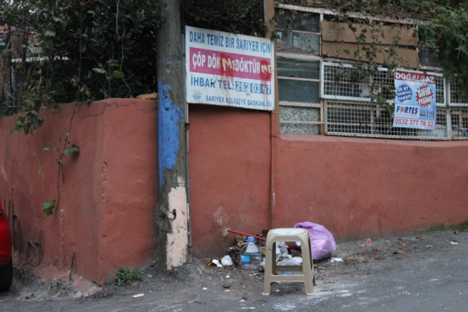 Ççöp dökmeyin uyarı levhasının altına bırakılmış çöpler